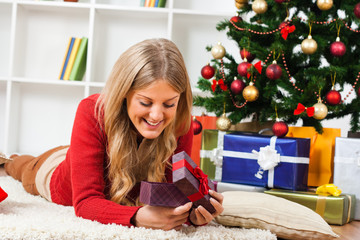 Young woman lying on carpet and opening Christmas present