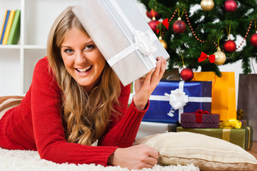 Beautiful young woman holding Christmas present