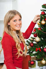 Beautiful young woman with Christmas tree
