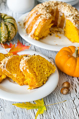 Glazed pumpkin cake with hazelnuts on white background
