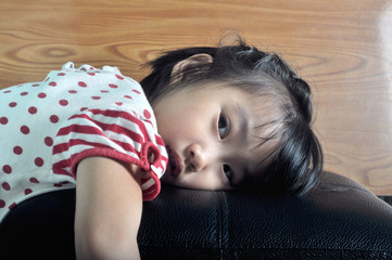 small asian child feel lonely in sofa