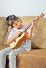 Asian little girl playing ukulele