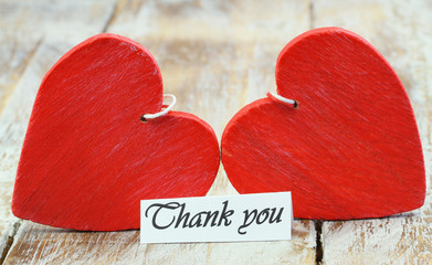 Thank you card with two read hearts on wooden surface