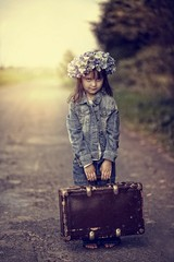 The little girl in a wreath of blue flowers and an old suitcase