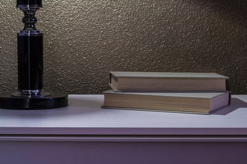 Book and bedside table with lamp.