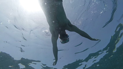 Man swimming on ocean surface view from below