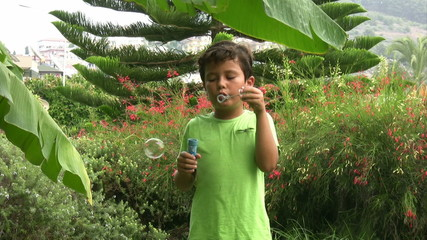 Happy child blowing bubbles in the garden