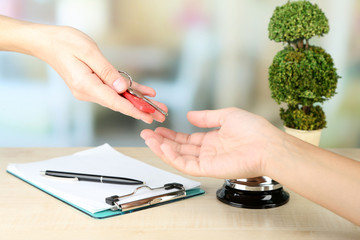 Female hand giving hotel key