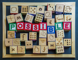 Colorful wooden word Impossible on blackboard