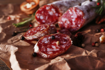 French salami and walnuts on craft paper background