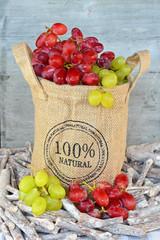 Natuurlijke tros rode en groene druiven in jute zak