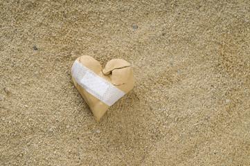 gebrochens Herz mit Pflaster im Sand