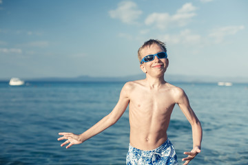 Funny little child playing in sea splashing water and jumping.