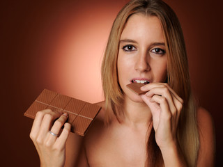 Young woman eating chocolate.