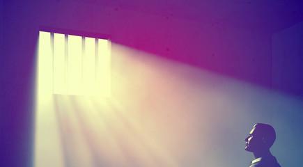 prisoner in dark room with light beams
