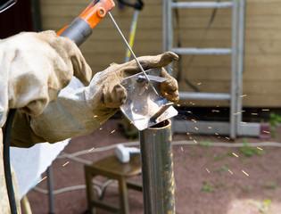 Welder, repairing the gardening equipment, country outdoor