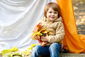 Девочка с кленовыми листьями в руках