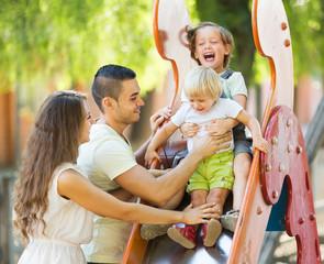 Smiling parents helping kids on slide