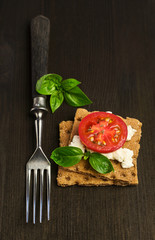 rye bread with cheese, tomatoes and basil with a fork