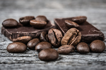 close up of coffee beans and  chocolate on gray  background