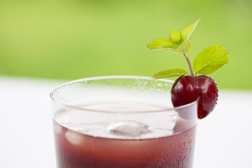 Glass of Cold cherries juice in garden