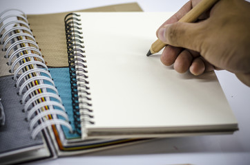 Close up image of hand which writing on blank notebook