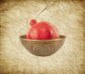 Pomegranate in ancient carved vase on old paper