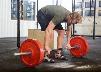 Man Picking Barbell in Gym