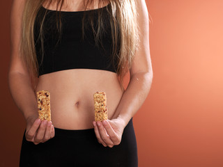 Young woman eating cereal bars.