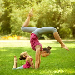 Mother and daughter doing exercise outdoors. Healthy lifestyle