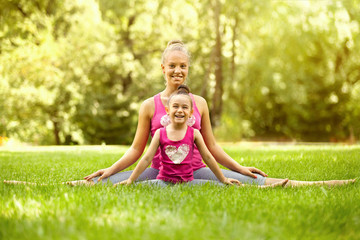 Sisters doing exercise outdoors. Healthy lifestyle
