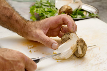 chef cutting boletus over chopping board