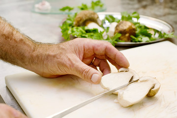 chef cutting boletus over kitchen top
