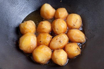 whole fried potatoes in oil in a cauldron