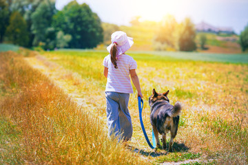 Little girl walking with dog at the meadow