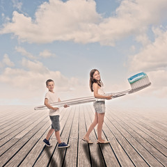 two children holding a big toothbrush on a wharf