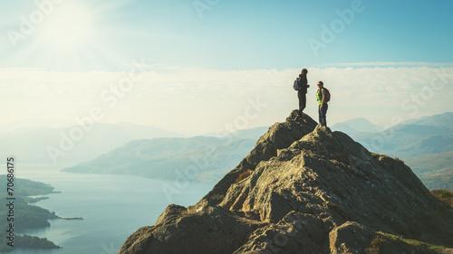 Leinwandbild Motiv Hikers on top of the mountain enjoying valley view, Scotland