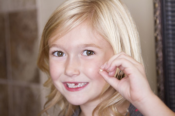 child holding her front tooth