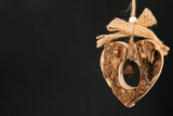 Bark wooden heart on a rope with little opaque brass bell poster