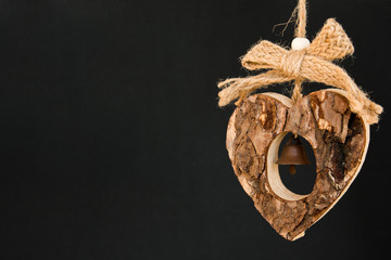 Bark wooden heart on a rope with little opaque brass bell