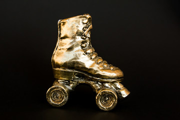 golden roller skate against black background