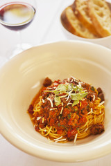 spaghettini Bolognese with a glass of white wine and bread