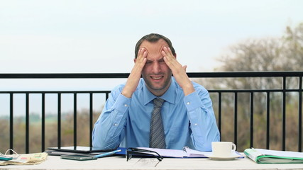 Tired businessman having headache during work on terrace