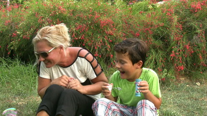 Mother and son blowing bubbles in the park