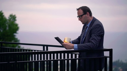 Businessman reading news on tablet computer on terrace in the ev