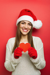 Beautiful young Santa woman with red paper heart