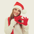 Beautiful young Santa woman gesturing heart