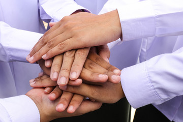 diverse group of workers with their hands together in form of te