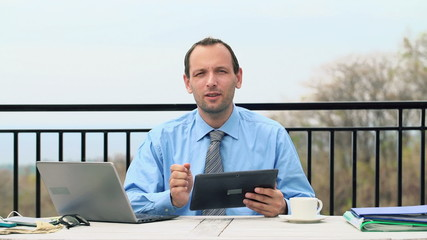 Businessman with tablet and laptop talking to camera on terrace