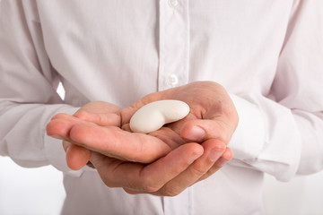Close Up of Man Holding White Heart in Hands